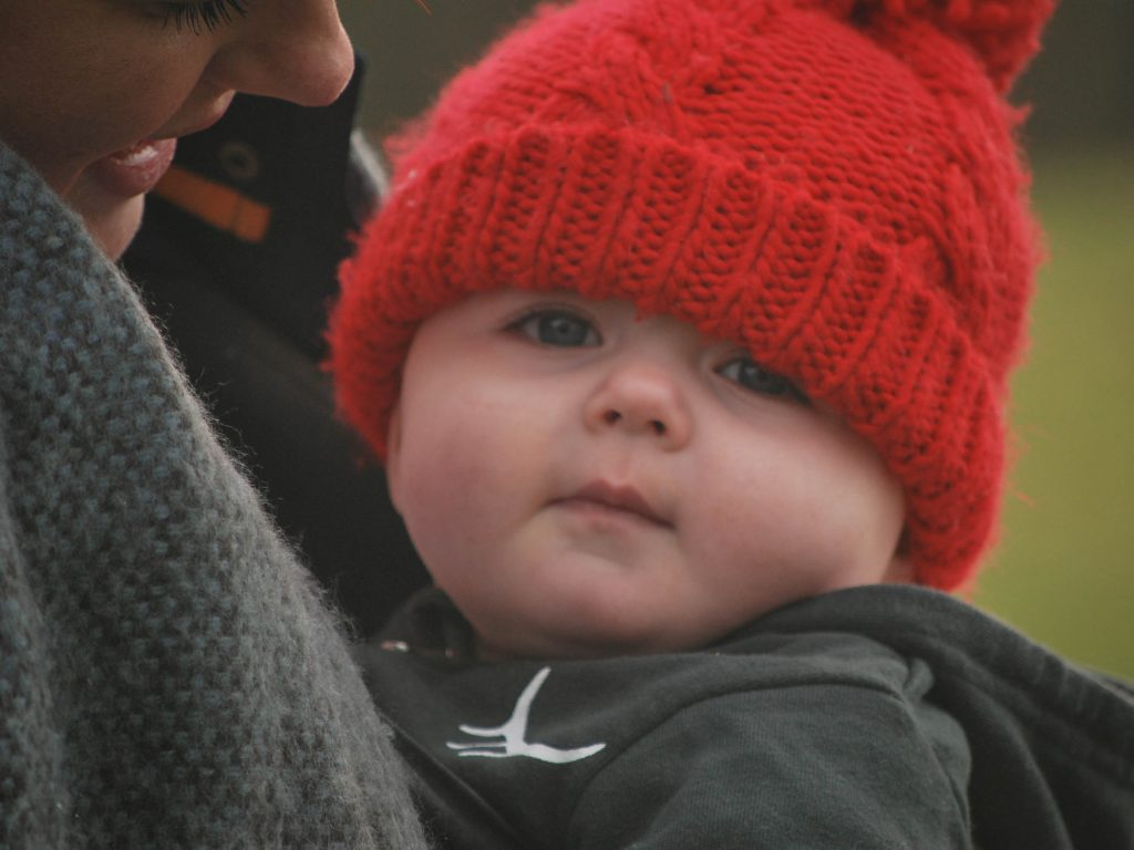 athena bundled in ergo with bobble hat on